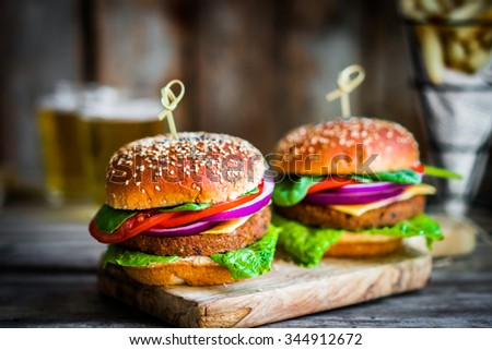 Homemade burgers on rustic wooden background - stock photo