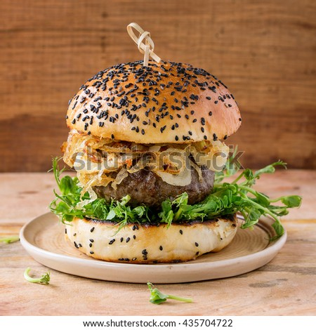 Homemade burgers with beef, fried onion and pea sprouts, served on ceramic plate over wooden textured background. Square image - stock photo