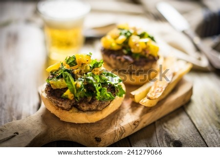Homemade burgers with fries on wooden background - stock photo