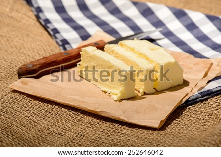 Homemade butter. Closeup image of a delicious sliced butter and knife on a craft paper and farm style checkered napkin  - stock photo