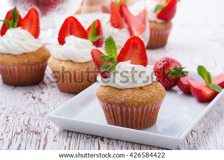 Homemade buttercream cupcakes with strawberries and fresh mint on white wooden table - stock photo
