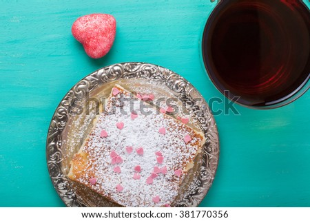 Homemade cake on a metal plate on colored wooden background.