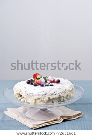 Homemade cake with fresh berries, icing sugar goes on top - stock photo