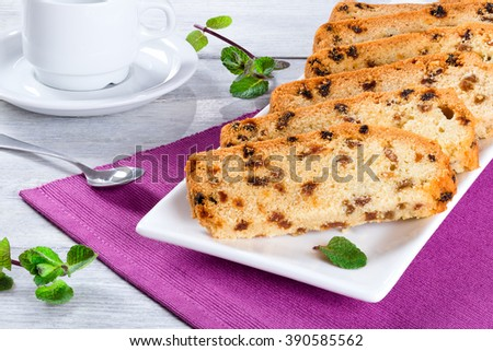 homemade cake with raisins in a basket, beautifully decorated with a ribbon and a lace, on a magenta table-napkin, cup of tea and spoon on a background, close-up - stock photo