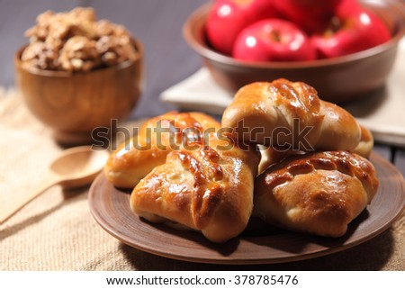 Homemade cakes are a large rustic pottery plate next to cup of nuts and a bunch of red apples on a rough table cloth on a wooden table. Selective focus - stock photo