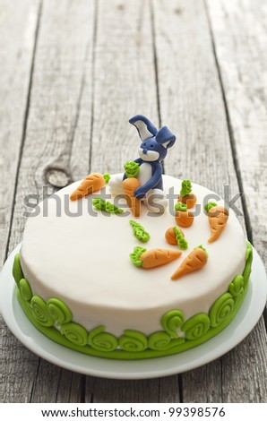 Homemade carrot cake with rabbit decoration on old wood table - stock photo