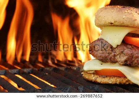 Homemade Cheeseburger Close-up On Flaming Barbecue Grill Background. Snack For Picnic or Outdoor Party. - stock photo