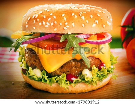 Homemade cheeseburger or burger on a sesame bun with a succulent ground beef patty, melting cheddar cheese, onion, rocket, tomato and lettuce, close up with vignetting - stock photo
