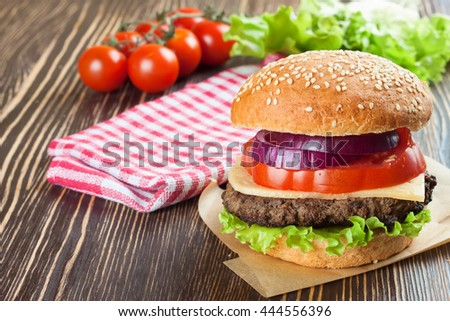 Homemade cheeseburger with beef patties and fresh salad on seasame buns, sered on brown wooden table. - stock photo
