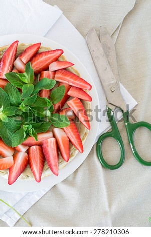 Homemade cheesecake decorated with fresh strawberries and mint on white plate on linen, top view - stock photo