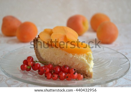 Homemade cheesecake with fresh apricot slices and red currants in the glass plate. Healthy summer breakfast. Soft focus. - stock photo
