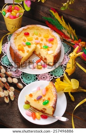 homemade cheesecake with raisins and egg shaped candies decoration for easter on wooden table - stock photo