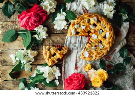 Homemade cherry and strawberry  pie on rustic background. Rustic dark style. decorated with roses and jasmine flowers. Dessert for the family