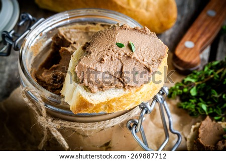 homemade chicken liver pate with fresh baguette closeup on rustic wooden table - stock photo