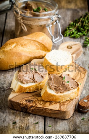 homemade chicken liver pate with fresh baguette on rustic wooden table - stock photo