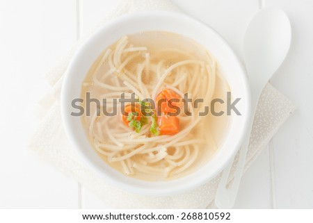 homemade chicken noodle soup with carrots, top view - stock photo