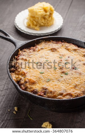 Homemade chili baked in cast iron skillet with side of cornbread - stock photo