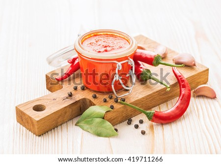 Homemade chili pepper hot sauce with ingredients - stock photo