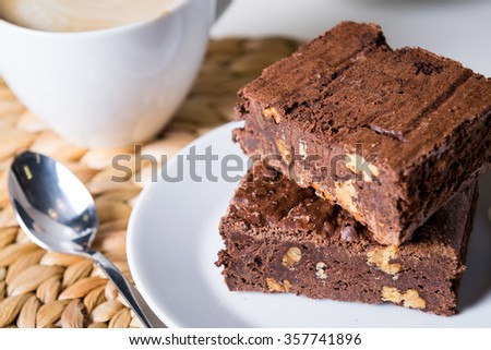 homemade chocolate brownies or chocolate cakes with nuts on white plate, cappuccino, close up - stock photo