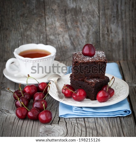 Homemade chocolate brownies with fresh berry and cup of tea on old wooden background, selective focus - stock photo