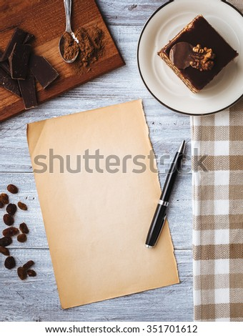 Homemade chocolate cake and blank old paper for recipe on wooden table. Toned photo. Top view. - stock photo