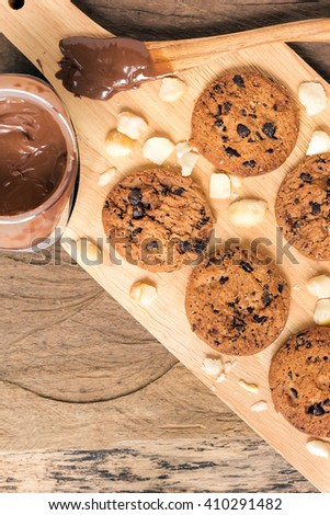 Homemade chocolate chip cookies and macadamia nut with melt chocolate serving wood platter - stock photo