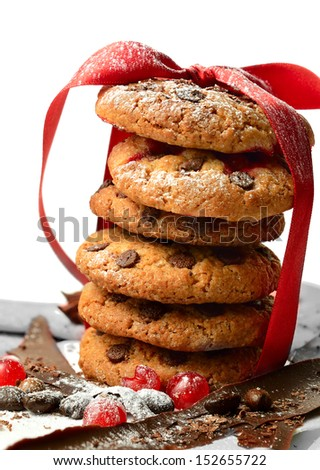 Homemade chocolate chip cookies stacked and tied with a ribbon on chocolate spears, coffee beans and redcurrants. Concept image for a cafe, a seasonal design or Valentines day concept. Copy space. - stock photo