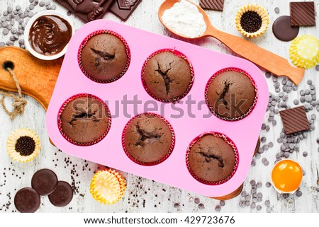 Homemade chocolate muffins on white table with ingredients. Baking food concept top view - stock photo