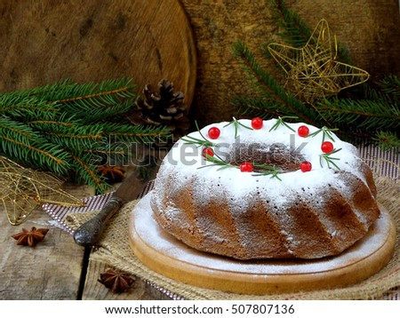 homemade christmas cake with cranberry and new year tree decorations frame on wooden table background. Rustic style.