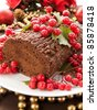 Homemade christmas chocolate yule log with wild berries. Shallow dof. - stock photo