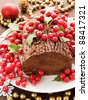 Homemade christmas chocolate yule log with wild berries. Shallow dof. - stock photo