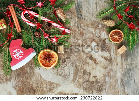 Homemade christmas gingerbreads painted as a red hat of Santa with snowflake, candy canes and candied orange on the wooden background with fir branches . Selective focus and place for text. Toned - stock photo