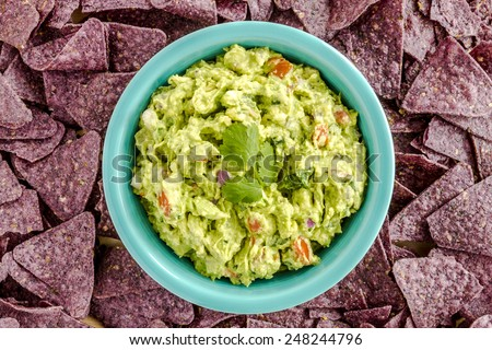 Homemade chunky guacamole in bright blue bowl surrounded by blue corn tortilla chips - stock photo