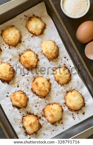 Homemade coconut macaroons (coconut meringue cookies) in baking pan, photographed overhead with natural light. Coconut macaroons are traditional Christmas cookies in Germany called Kokosmakronen. - stock photo
