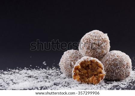 Homemade coconut rum balls on a black background