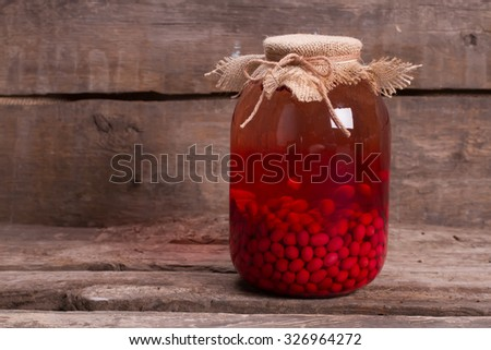 Homemade compote of dogwood on wooden boards. Natural drink on an old wooden shelf. Canning juice in the cellar. - stock photo