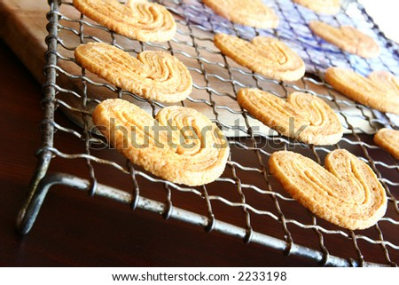 Homemade cookies on a cooling rack.  Very shallow D.O.F - cookie in the front are in focus, background out of focus. - stock photo