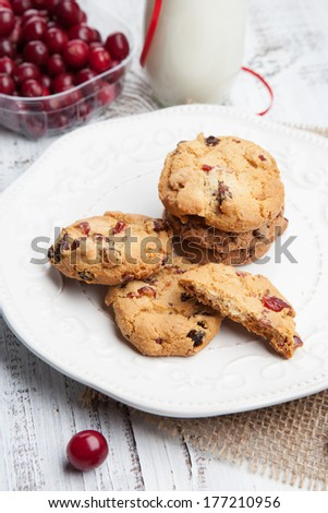 Homemade cookies with cranberries and a milk on a white wooden table - stock photo