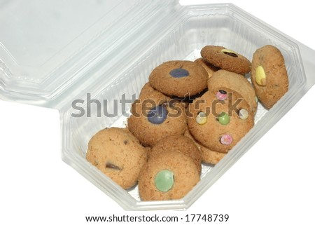 Homemade cookies with melted candies packed in a plastic box - stock photo