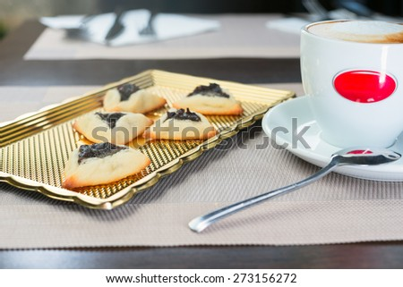 homemade cookies with prunes lying on a tray next to a cup of coffee