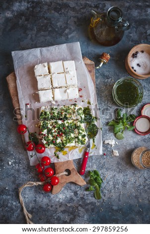 Homemade Cottage Cheese cut into cubes with pesto sauce and cherry tomatoes served over on a cooking paper with vintage cutting board from above above. Rustic dark styling.  - stock photo