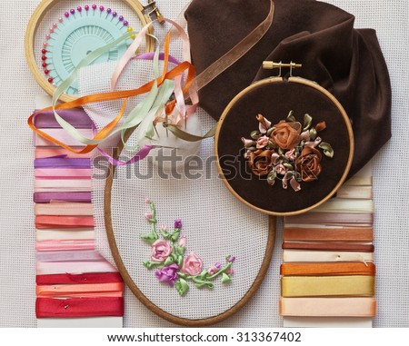 Homemade crafts. Process embroidery satin ribbons. Accessories for embroidery: needle, ribbon, canvas, tambour  - stock photo