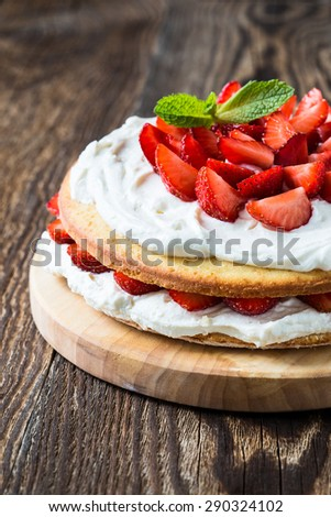 Homemade cream layer cake, fresh, colorful, and delicious dessert with juicy strawberries,  sweet whipped cream and cream cheese - stock photo
