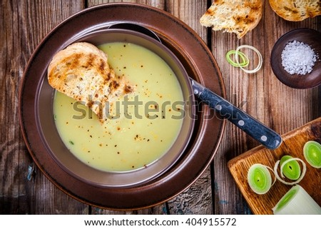 homemade cream soup of leek with toasts on a wooden background - stock photo