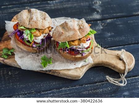 Homemade crispy fish burger on a dark  rustic wooden board - stock photo