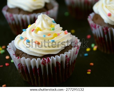 Homemade cupcakes on dark wooden background
