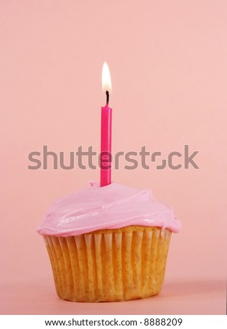 homemade cupcakes with pink icing and candle