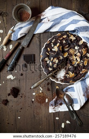 homemade dark chocolate and almonds cake on wooden table with cloth and utensils - stock photo