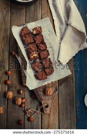 Homemade dark chocolate with nuts fudge ready to eat over rustic kitchen table. Toned image. - stock photo