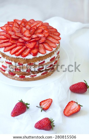 Homemade delicious birthday strawberry sponge cake decorated with fresh strawberries on white kitchen table background. Rustic style and natural light - stock photo